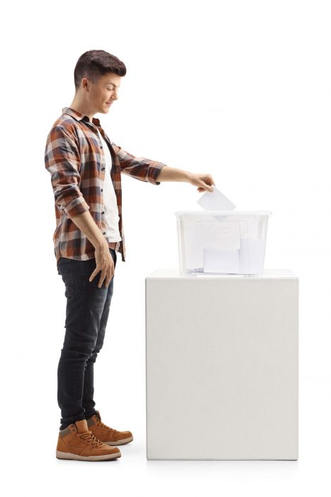 Full Length Profile Shot Of A Young Guy Voting On Elections